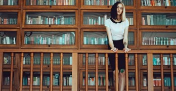 Ways to Include Libraries in Book Marketing woman by library shelves