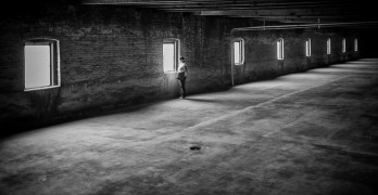 woman in empty warehouse poetic voices